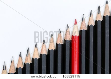 Red Pencil Standing Out From Crowd Of Plenty Identical Black Fellows