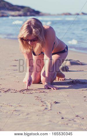 Blond Girl Handwriting On Sand