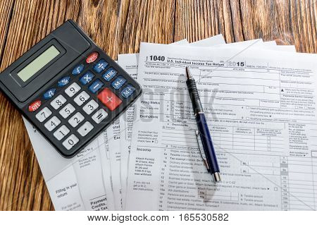 Tax form 1040 with pen and calculator on the table