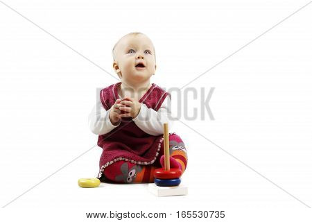 Shot of an adorable baby girl in red clothes playing with some wooden toys, looking up, isolated over white background.