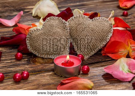 Vintage hearts with petals and candle on the table