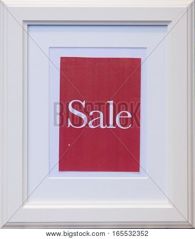word Sale in white letters on red background of small classic picture frame