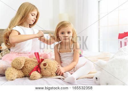 Pretty ender sister is combing hair of small girl. Kid is looking at camera with joy while sitting on bed with teddy bear