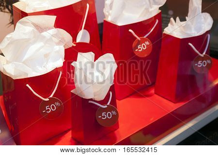 red paper bags with sale signs in display window of shop