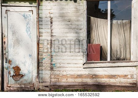Close up view of old wooden broken window and door with painting color peeled off. Flaking paint on broken window and worn door of abandoned house as vintage wood background texture. Abandoned brick house wall as vintage background.