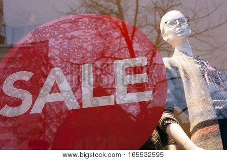 sale sign on shop window and fashion doll in the store displays clothes