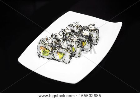 Sushi rolls set with crab meat and avocado sprinkled with black sesame seeds on a black background