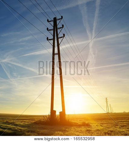 Silhouette electricity transmission pylons in the sunset.