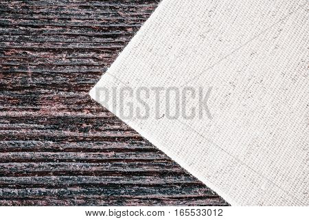 Combined background of light undyed linen fabric and dark wood. Macro view