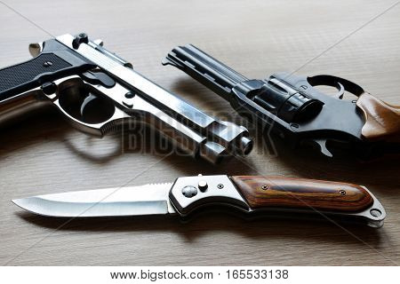 Black revolver pistols with knife on wooden board.