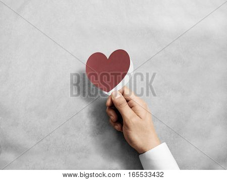 Hand holding blank red valentine's card mockup. Arm opening paper love invitation, design mock up. Holiday greeting postcard presentation. Person showing amour handmade postal.