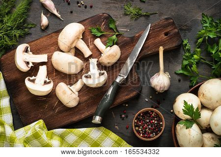 Sliced mushrooms and ingredients for cooking at dark wooden table. Space for text. Ingredients for cooking food background.