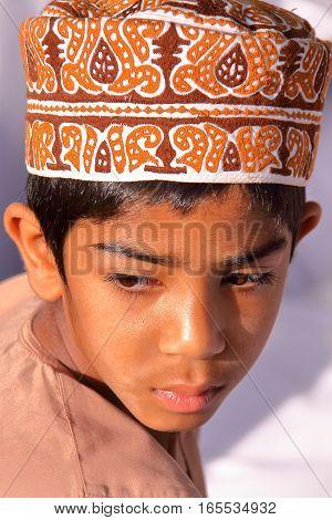 NIZWA, OMAN - FEBRUARY 3, 2012: Portrait of a little Omani boy traditionally dressed attending the Goat Market
