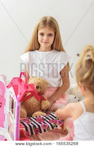 I like playing with my sister. Happy girl is sitting on bed near toys and looking at camera with joy. She is smiling