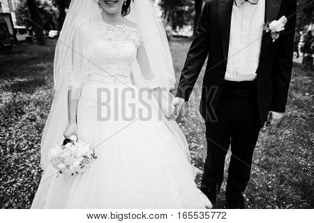 Newlyweds Holding Hand At Their Wedding Day. Black And White Photo