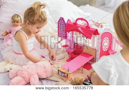 Pretty little child is enjoying game in doll house with her elder sister. She is sitting on bed and smiling