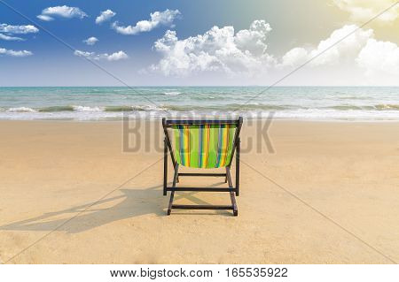 Beach chair and shadow on the white sand beach with sunset light sky Summer background (lonely concept)