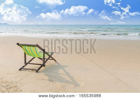 Beach chair on the sand with summer Summer background. Summer fresh concept. Lonely in summer beach. Selective focus on chair.