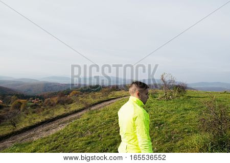 Young handsome hipster athlete in yellow sports jacket running in sunny autumn nature