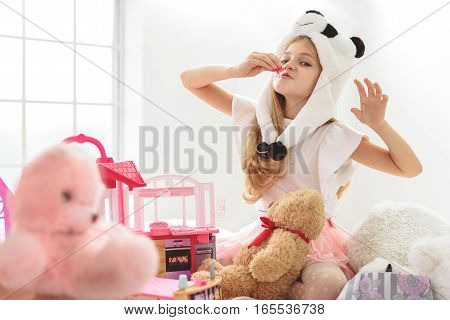 Happy female child is playing at home with toys. He is wearing panda hat and looking at camera with joy
