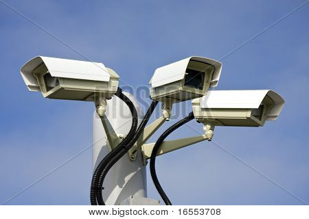 Security cctv cameras in front of blue sky