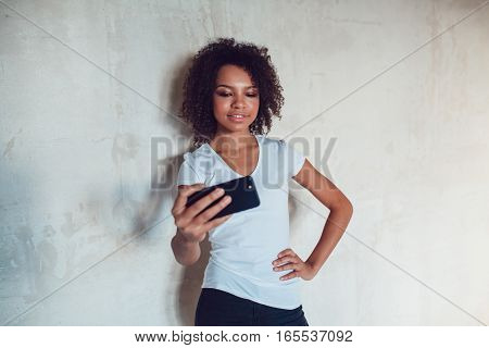 Beautiful smiling african girl make selfie on grey background