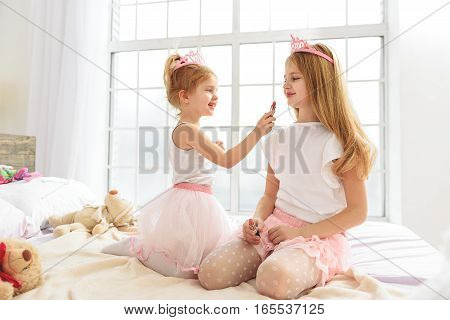 Pretty two sisters are playing in princesses at home. Small girl is applying lipstick on female lips and laughing