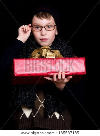 small boy or cute nerd kid in glasses hat and fashionable knitted scarf on black background holds red present box with golden bow