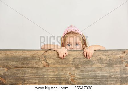 Pretty girl is peeping through wooden fence with interest. She has princess crown on her head. Isolated