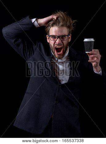 handsome bearded stylish angry business man in elegant black suit in glasses holding cup of coffee with raised hand in studio on black background