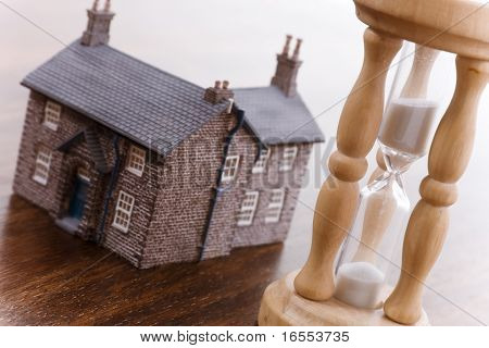 Real estate concept time running out focus on hourglass