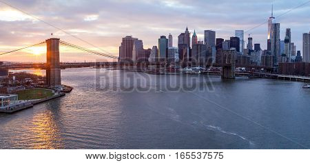 New York City panorama landscape scene at sunset with Brooklyn Bridge over the East River and Lower Manhattan skyline skyscrapers