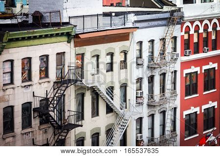New York City view of historic apartment buildings with windows rooftops and fire escapes along Bowery street in the Chinatown neighborhood of Manhattan NYC