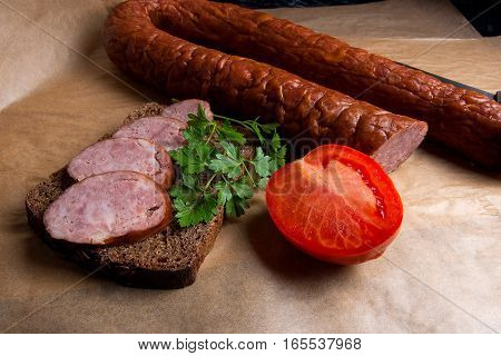 Slices Of Smoked Sausage With Spice, Herbs And Vegetables On The Packaging Paper.