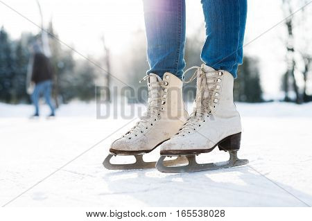 Legs of unrecognizable woman in sunny winter nature ice skating, close up.
