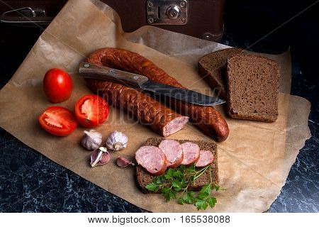 Slices Of Smoked Sausage With Spice, Herbs And Vegetables On The Packaging Paper. Vintage Knife.
