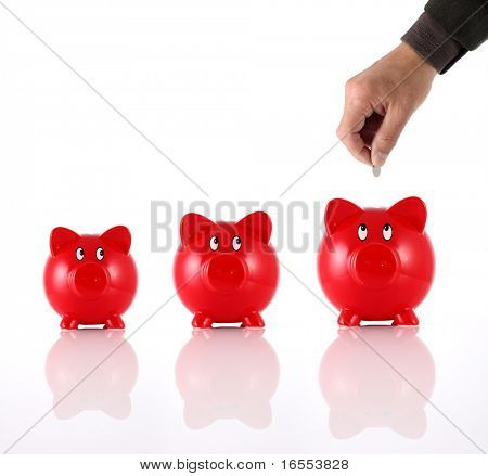 Hand putting coin into three hopeful piggy banks