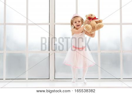 Happy little girl is playing with teddy bear and laughing. She is jumping near window in pink dress and crown