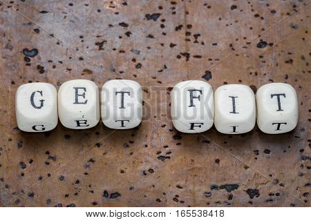 Get fit text on wooden cubes on a brown cork background