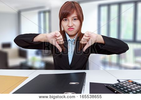 Unhappy business woman with thumb down in office - calculator file and document on desk
