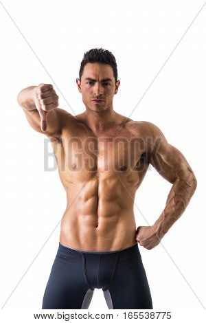 Disappointed or displeased muscular young man doing thumb down sign