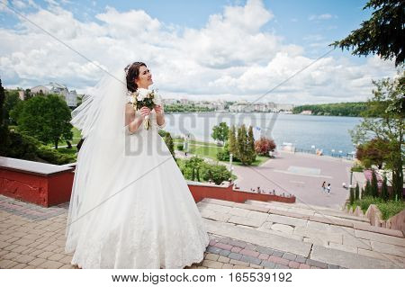 Cheerfull Brunette Bride Against Blue Sky With Amazing Clouds Background City Lake.