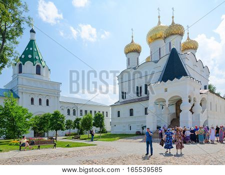 KOSTROMA RUSSIA - JULY 20 2016: Unidentified people visit Holy Trinity Ipatievsky male monastery in Kostroma. On the left - Gate Church of Chrysanth and Daria (XIX century) on the right - Trinity Cathedral