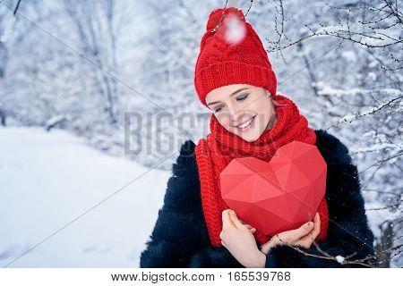 Love and valentines day concept. Closeup portrait of lovely woman holding red polygon paper heart shape huging it with tenderness over winter landscape