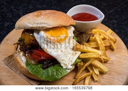 Homemade cheese burger with bread, egg, french fries and sauce on wooden plate