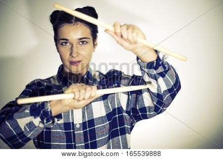 Beautiful girl. Girl holding drumsticks. Girl holding drum sticks on a white background. Drumsticks