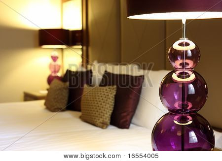 Abstract luxury hotel room with focus on foreground electric lamp