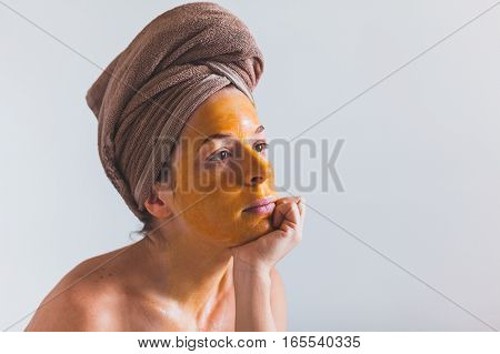 Young woman with an egg mask on her face