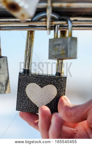 Hand touches padlock with heart pattern. Checking the strength of the concept