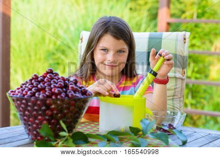 stoning fresh cherries by young pretty girl in the garden - using cherry pitter